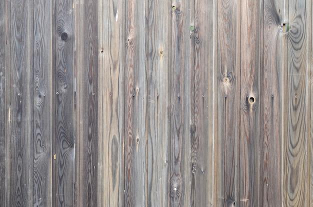 美しい抽象的な穀物の表面を持つ古いグランジダークブラウンの木製パネルパターン