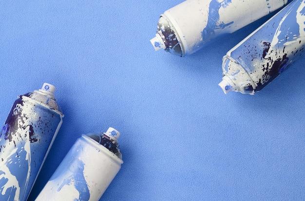 ペンキのしずくが付いている青いエアゾールスプレー缶は柔らかく毛皮のような青いフリース生地の毛布の上にあります