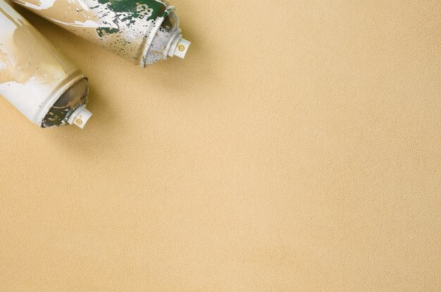 いくつかの使用済みオレンジ色のエアゾールスプレー缶にペンキのしずくが付いている