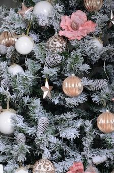 クリスマスツリーを飾ることをクローズアップ。装飾電球、雪に覆われた緑のモミの木