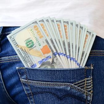 女の子のジーンズの後ろのポケットにたくさんのドル紙幣があります