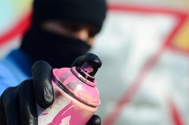 Молодой художник граффити в синей куртке и черной маске держит банку с краской