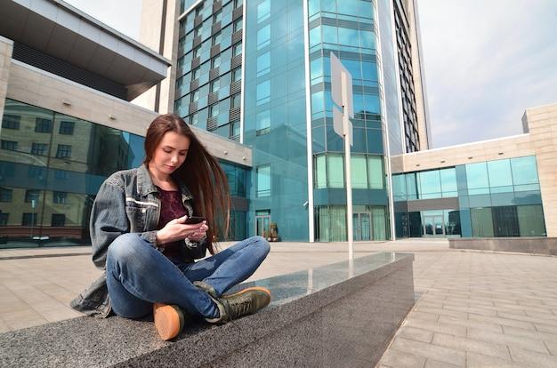 若い女の子は事務所ビルの背景にスマートフォンを使用しています