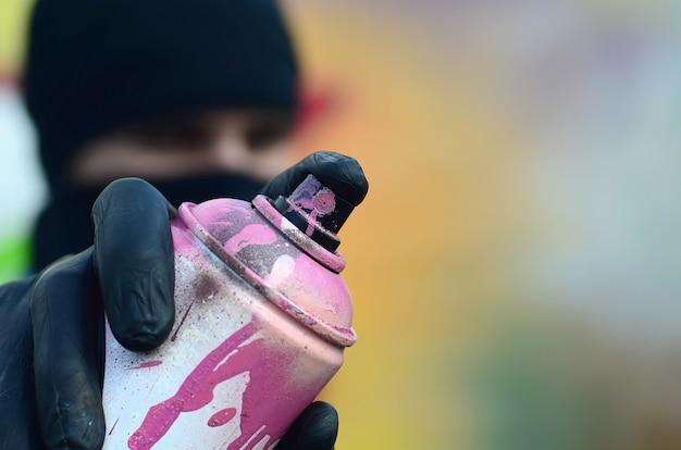 青いジャケットと黒いマスクの若い落書きアーティストがペンキ缶を持っています。