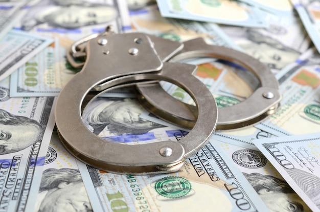 Серебряные полицейские наручники лежат на многих долларовых купюрах