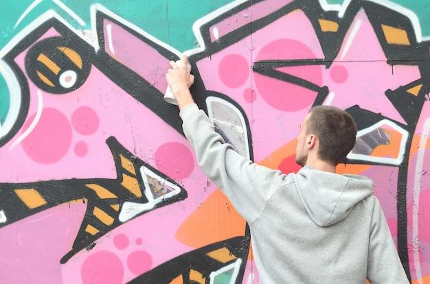 Молодой парень в серой толстовке рисует граффити
