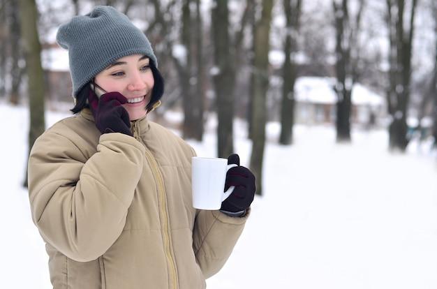 スマートフォンとコーヒーカップを持つ若い女の子の冬の肖像