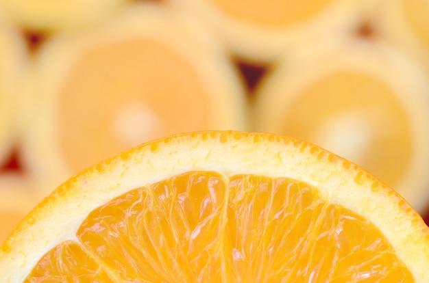 多くのぼやけたオレンジスライスの背景にオレンジ色の果物のスライスのフラグメント