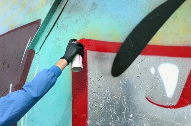 隠された顔を持つ若いフーリガンは、金属製の壁に落書きを描きます。