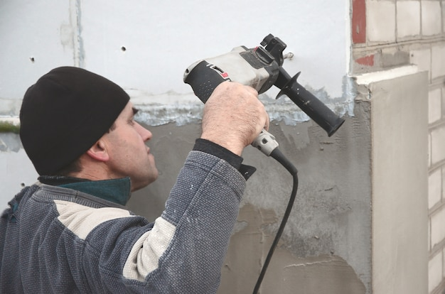 Пожилой рабочий сверлит отверстие в стене из пенопласта для последующей установки пластикового дюбеля.