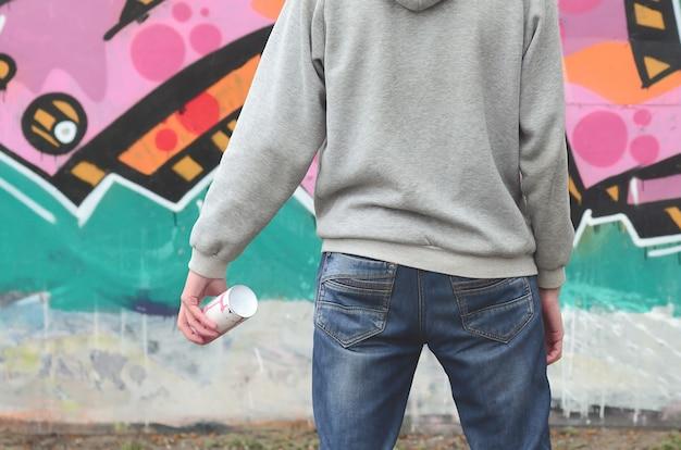 Молодой художник граффити в серой толстовке смотрит на стену