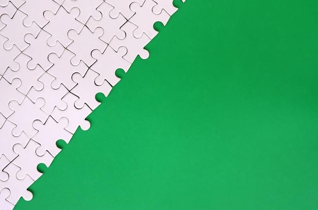 Фрагмент сложенной белой головоломки на фоне зеленой пластиковой поверхности