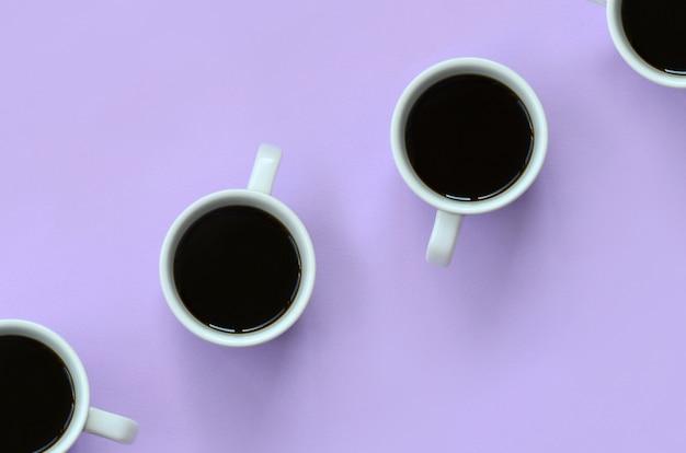 Много маленьких белых кофейных чашек на текстуре пастельно-фиолетового цвета