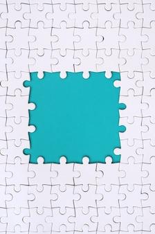 青いスペースの周りに白いジグソーパズルで作られた長方形の形でフレーミング
