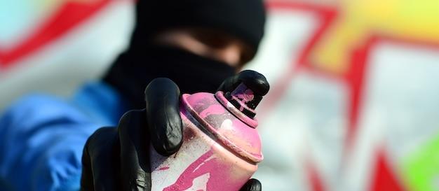 青いジャケットと黒いマスクの若いグラフィティアーティストがペンキ缶を持っています。