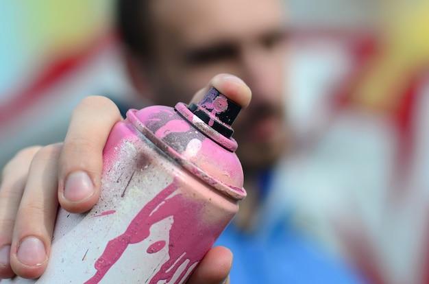 青いジャケットを着た若いグラフィティアーティストがペンキ缶を持っています。