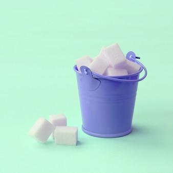 ターコイズブルーのパステルカラーの上に砂糖の立方体がいっぱい入ったミニチュアライラックバケツ