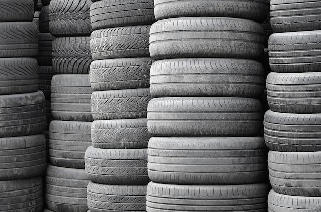 二次自動車部品店のガレージで高い山と積み重ねられた古い中古タイヤ