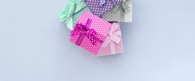 Куча маленьких цветных подарочных коробок с лентами лежит на фиалке
