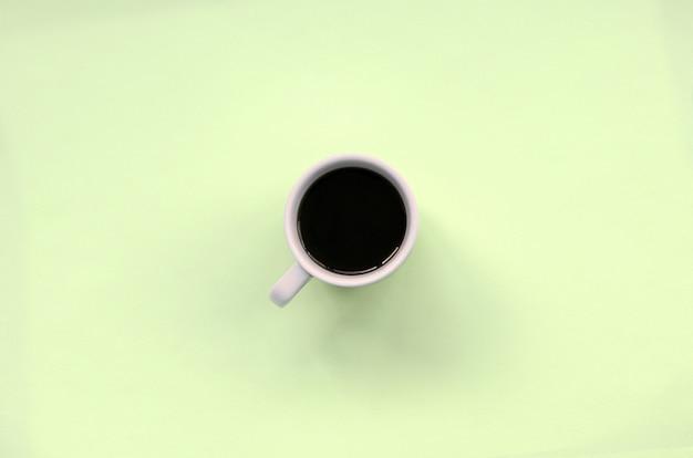 Маленькая белая кофейная чашка на фактуре модной пастельной салатовой бумаги