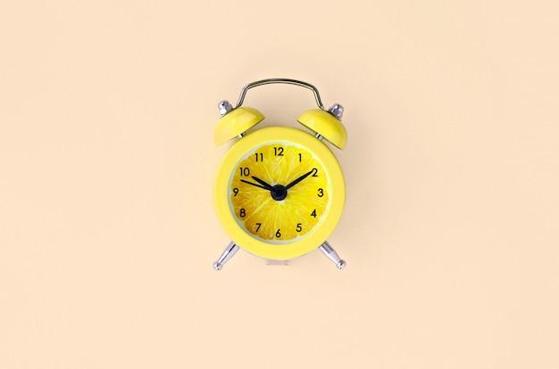 小さな黄色の目覚まし時計で新鮮なレモンスライス