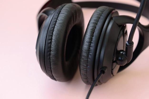 Концепция прослушивания музыки. черные наушники лежат на розовом