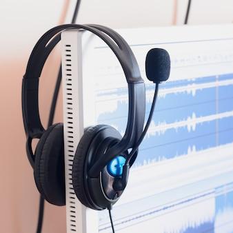 サウンドデザイナーの木製デスクトップに横たわる大きな黒いヘッドフォン