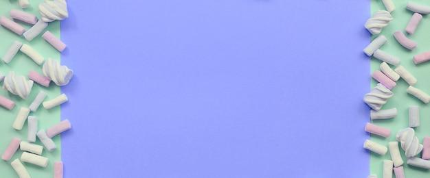 緑と薄紫色の紙の背景に広げてカラフルなマシュマロ