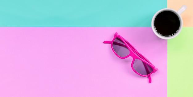 小さな白いコーヒーカップとファッションパステルピンク、ブルー、サンゴ、ライムの色の背景にピンクのサングラス