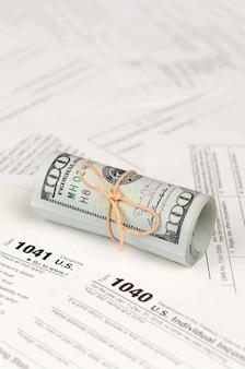 Налоговые формы лежат рядом рулон стодолларовых купюр. декларация о подоходном налоге