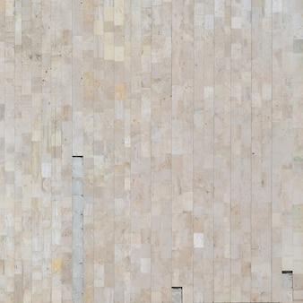 さまざまな大きなタイルから古いベージュの大理石の壁