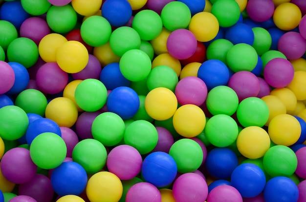 楽しさと色のプラスチックボールバックグラウンドでジャンプのスイミングプール