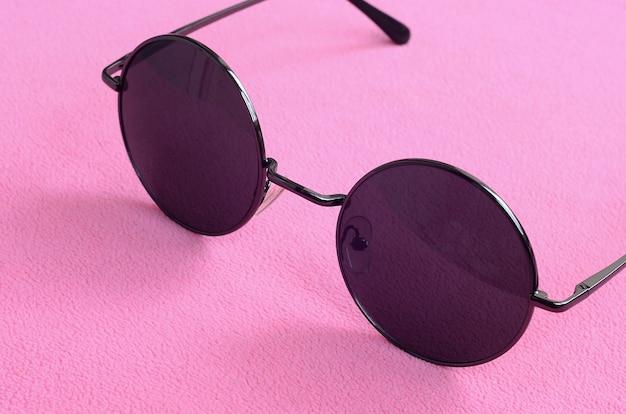 ラウンドグラスとスタイリッシュな黒のサングラスは、柔らかくふわふわのライトピンクフリース生地で作られた毛布の上にあり