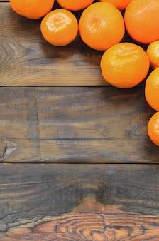 茶色の木製の背景の上に横たわる多くの新鮮なオレンジ