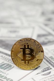 Золотая монета биткойн на фоне купюры долларов