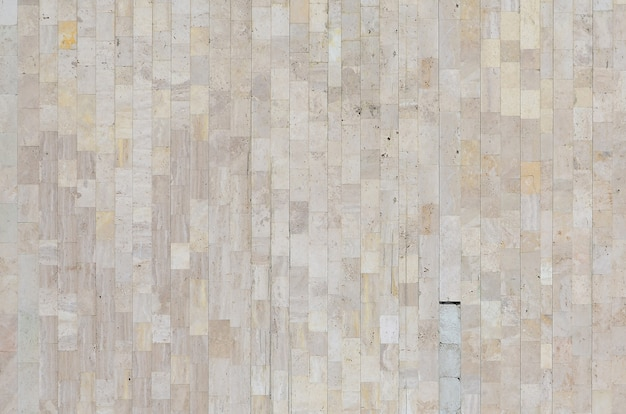 さまざまな大きなタイルから作られた古いベージュの大理石の壁のテクスチャ