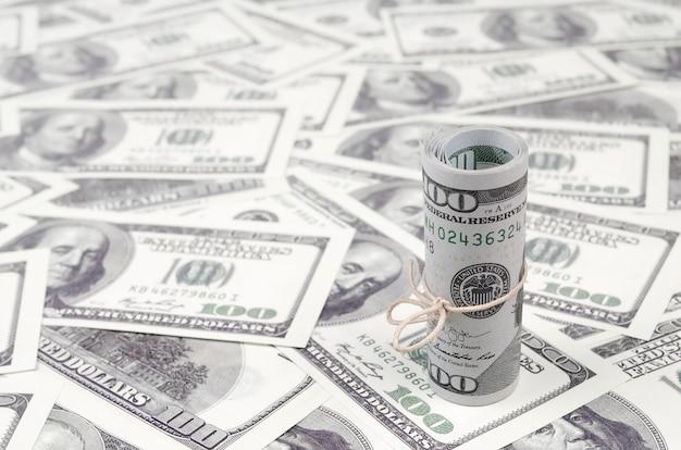 米ドルはロールバックされ、背景がぼやけたアメリカの紙幣の多くの上にあるバンドで締められます