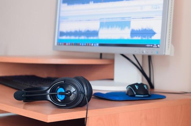 コンピューターの画面と木製のデスクトップに横たわっている大きな黒いヘッドフォン