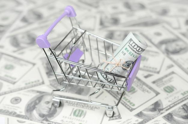 Маленькая тележка для покупок с долларовыми банкнотами. концепция кэшбэка и сделок на продажу