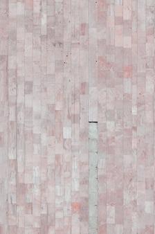 さまざまな大きなタイルから古いベージュの大理石の壁の背景テクスチャ