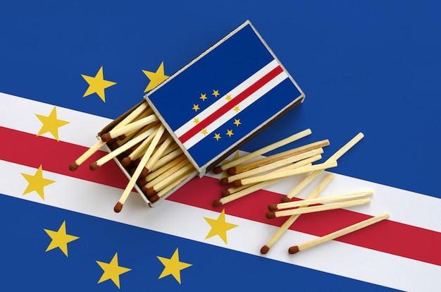 カボベルデの旗が開いているマッチ箱に表示され、そこからいくつかのマッチが落ち、大きな旗の上に横たわる