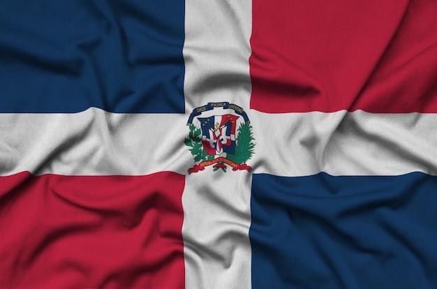 Флаг доминиканской республики изображен на спортивной ткани с множеством складок.