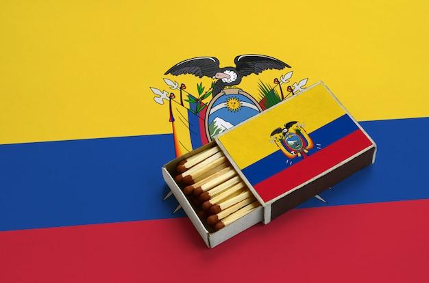 エクアドルの旗は開いているマッチ箱に表示され、マッチで満たされ、大きな旗の上にあります