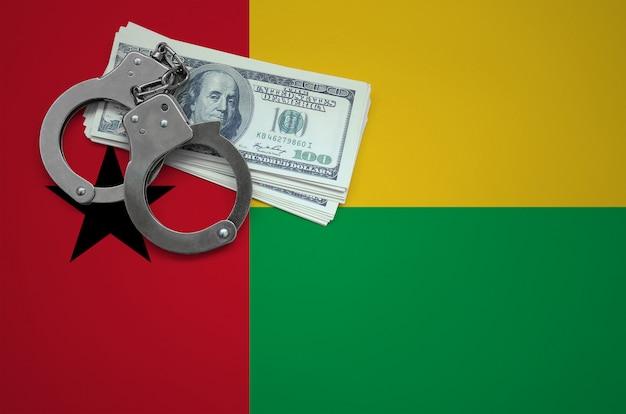 手錠とドルの束とギニアビサウの旗。法律を破り、犯罪を犯すという概念