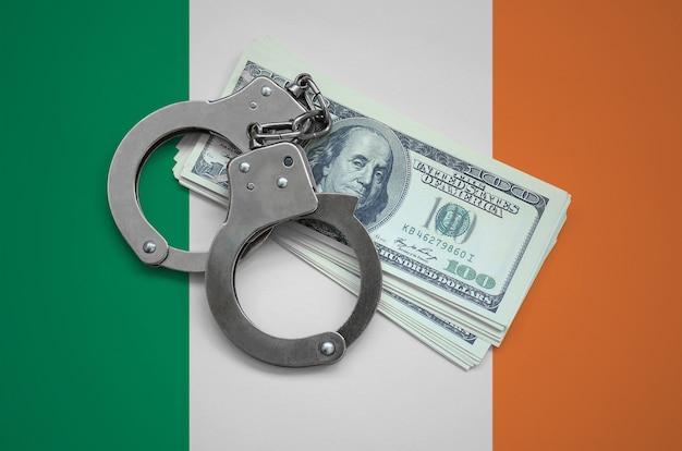 Флаг ирландии с наручниками и пачкой долларов. валютная коррупция в стране. финансовые преступления