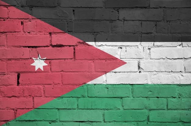 古いレンガの壁にヨルダンの国旗が描かれています
