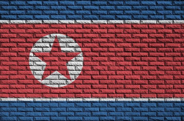 北朝鮮の旗が古いレンガの壁に描かれています