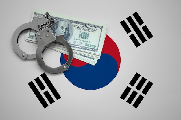 手錠とドルの束で韓国国旗。法律を破り、犯罪を犯すという概念