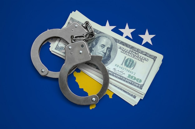 手錠とドルの束とコソボの旗。国の通貨の腐敗。金融犯罪