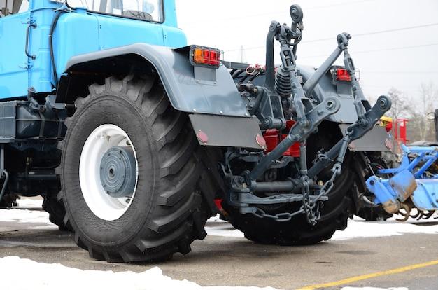 雪の降る天気の新しいトラクターの背面図の車輪